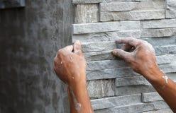 El trabajador instala la superficie de la pared de piedra con el cemento para la casa Foto de archivo libre de regalías