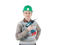 El trabajador joven celebra un taladro en su mano Imagen de archivo