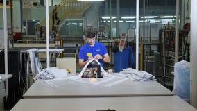 El trabajador joven conecta el sello del refrigerador con la herramienta en la tabla metrajes