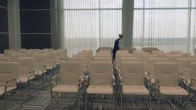 El trabajador joven del aeropuerto en la sala de conferencias comprueba el cuarto almacen de metraje de vídeo