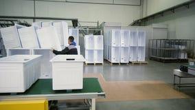 El trabajador joven pone la caja interna del refrigerador para llenar en almacén almacen de metraje de vídeo