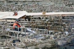 El trabajador limpia la fuente delante de la protección del invierno Imagenes de archivo