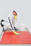 El trabajador limpia los azulejos rojos Imagenes de archivo