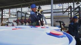 El trabajador llena los tanques azules del tubo del metal en el área de la planta metrajes