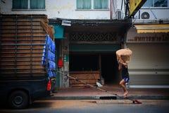 El trabajador lleva la cesta por el hombro Imagenes de archivo