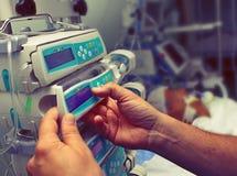 El trabajador médico configura el equipo en ICU imagen de archivo