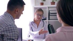 El trabajador médico dice buenas noticias sobre salud de una pareja casada los jóvenes en oficina en la tabla metrajes