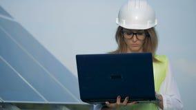 El trabajador magnífico de la señora está caminando con su ordenador portátil cerca de una batería solar almacen de metraje de vídeo