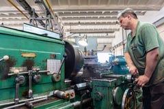 El trabajador maneja el equipo de la cortadora Trabajo de torneado en la producción foto de archivo