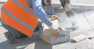 El trabajador maneja la piedra en la calle de la ciudad metrajes