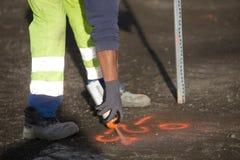 El trabajador marca un punto en el asfalto con la pintura de espray fluorescente Foto de archivo