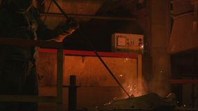 El trabajador mezcla el metal fundido con la pala especial en la planta almacen de metraje de vídeo