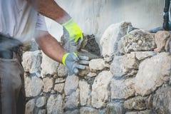 El trabajador monta una pared de piedra en un sitio tradicional de la renovación Fotos de archivo libres de regalías
