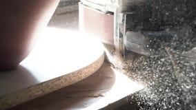 El trabajador muele la artesanía en madera con la máquina de pulir con el serrín que vuela en los lados, profesión, concepto de l almacen de video