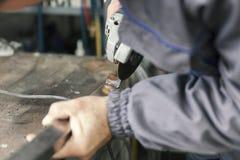 El trabajador muele las barras de metal Imagen de archivo