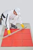 El trabajador nivela medida de los azulejos Fotos de archivo libres de regalías