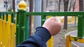 El trabajador pinta con una brocha verde una cerca del metal hecha de barras amarillas y verdes almacen de metraje de vídeo
