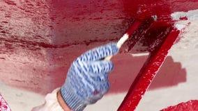 El trabajador pinta el metal del color rojo del propulsor de la nave en el astillero en el puerto de Moscú metrajes