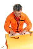El trabajador plegable cuidadosamente una hoja de papel Imagen de archivo libre de regalías