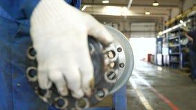 El trabajador pone el detalle largo del metal en el cilindro enorme del camión almacen de video