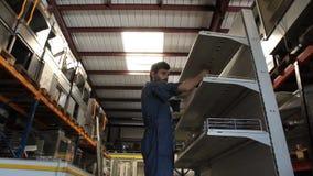 El trabajador pone el estante en soporte almacen de metraje de vídeo