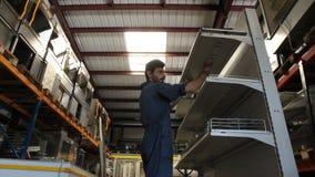 El trabajador pone el estante en soporte almacen de video
