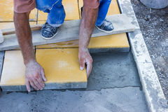El trabajador pone las pavimentadoras concretas 3 Imagen de archivo