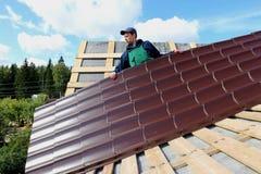 El trabajador pone las tejas del metal en el tejado Fotografía de archivo libre de regalías