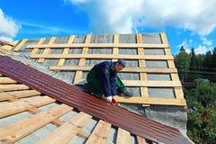 El trabajador pone las tejas del metal en el tejado Fotos de archivo libres de regalías