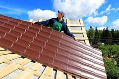 El trabajador pone las tejas del metal en el tejado Imagen de archivo