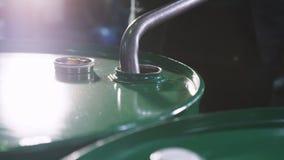 El trabajador pone el tubo en vueltas del tanque que el golpecito vierte la gasolina en la planta almacen de metraje de vídeo
