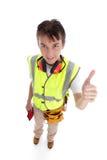 El trabajador positivo del constructor del aprendiz manosea con los dedos para arriba Foto de archivo