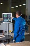 El trabajador presiona los botones del cristal Imagen de archivo libre de regalías