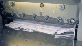 El trabajador puso el papel en la máquina industrial del corte de papel 4K metrajes