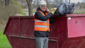 El trabajador que habla en el teléfono elegante y guarda el bolso de basura en el recipiente para residuos metrajes