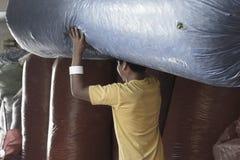 El trabajador que mueve hacia fuera un saco grande de coca se va por completo en Coca Leaves Depot en Chulumani, Sud Yungas, Boli Fotos de archivo libres de regalías