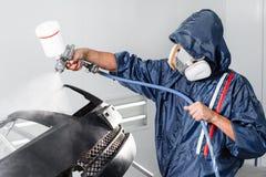 El trabajador que pinta un espacio en blanco del negro del coche parte en garaje especial, traje que lleva y engranaje protector Fotos de archivo