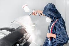 El trabajador que pinta un espacio en blanco del negro del coche parte en garaje especial, traje que lleva y engranaje protector Imagen de archivo libre de regalías