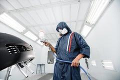 El trabajador que pinta un espacio en blanco del negro del coche parte en garaje especial, traje que lleva y engranaje protector Imagen de archivo