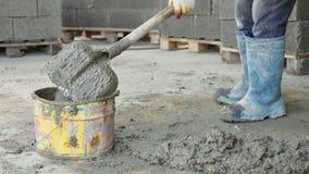 El trabajador que traspala mezclando un hormigón y lo pone en cubo en el emplazamiento de la obra Imagenes de archivo