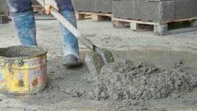 El trabajador que traspala mezclando un hormigón y lo pone en cubo en el emplazamiento de la obra Fotografía de archivo libre de regalías