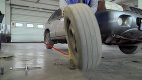El trabajador quita la rueda del coche almacen de metraje de vídeo