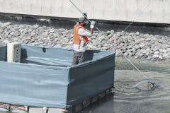 El trabajador quita la vegetación de la ruina y de la flotación del lago fotos de archivo libres de regalías