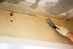 El trabajador raspa la pintura vieja Fotografía de archivo