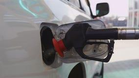 El trabajador reaprovisiona el coche de combustible blanco moderno con el primer del arma almacen de metraje de vídeo