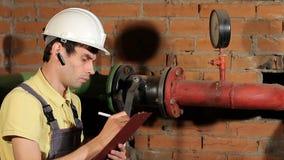 El trabajador registra las lecturas del manómetro en el tablero lecturas de contador de la toma descontentado con el resultado metrajes