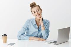 El trabajador remoto independiente de sexo femenino sonriente bonito lleva los vidrios usando el café de consumición del ordenado fotografía de archivo libre de regalías