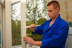 El trabajador repara una ventana Imagen de archivo libre de regalías