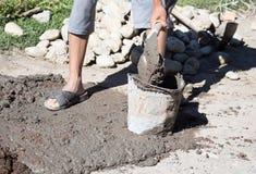 El trabajador revuelve la pala concreta Imagen de archivo