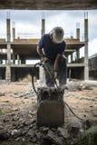 El trabajador rompe el hormigón con un martillo neumático - 2017 imágenes de archivo libres de regalías